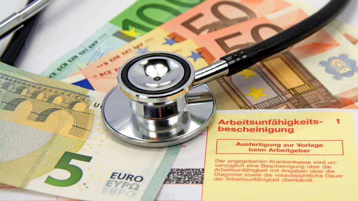 Stethoskop liegt auf einer Arbeitsunfähigkeitsbescheinigung sowie vier verschiedenen Euro-Scheinen