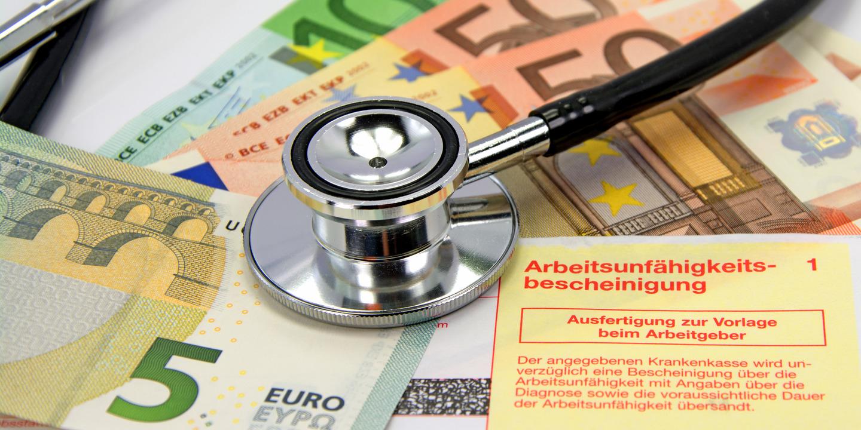 Stethoskop liegt auf einer Arbeitsunfähigkeitsbescheinigung und Geldscheinen im Wert von fünf, fünzig und hundert Euro