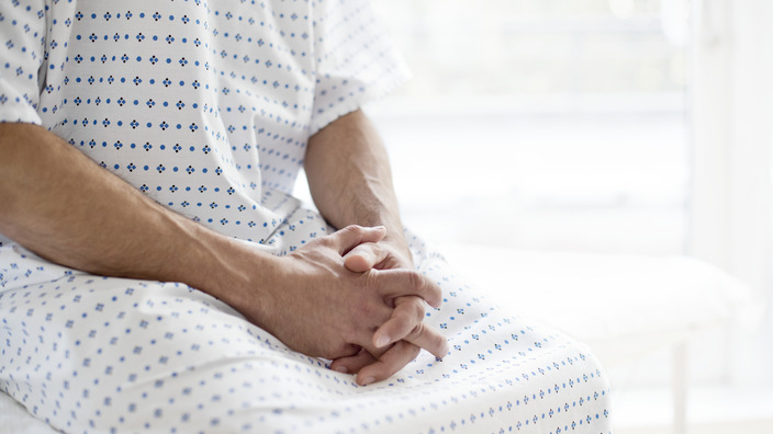 Patient sitzt im OP-Kittel auf dem Rand eines Krankenhausbettes
