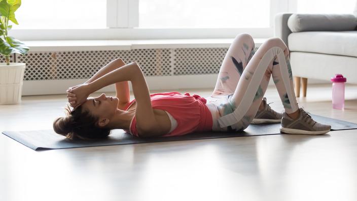 Junge Frau führt rücklings eine Fitnessübung auf einer Sportmatte aus