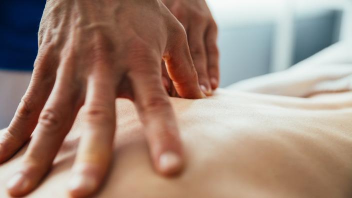 Massierende Hände auf Rücken