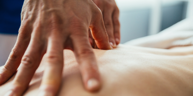 Hände eines Therapeuten behandeln Rücken eines Patienten.