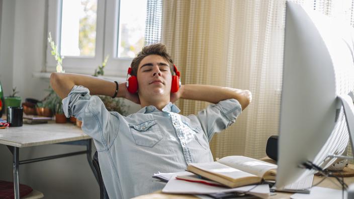 Junger Mann mit roten Kopfhörern sitzt am Schreibtisch und entspannt.