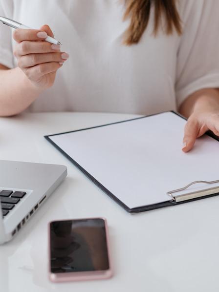 junge Frau recherchiert am Laptop und macht sich Notizen