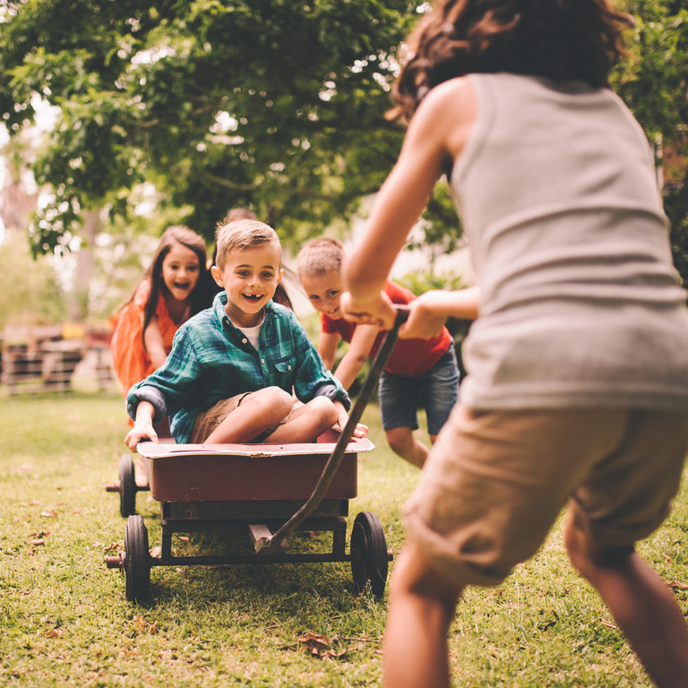 Vier Kinder spielen mit einem Bollerwagen