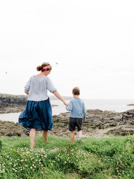 Mutter und Sohn wandern entlang eines Feldweges an der Küste