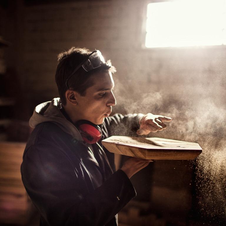 Schreiner pustet Holzstaub von einem Werkstück