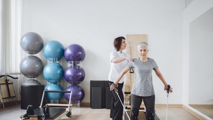 ältere Frau absolviert Pilatesübungen mit einer Trainerin