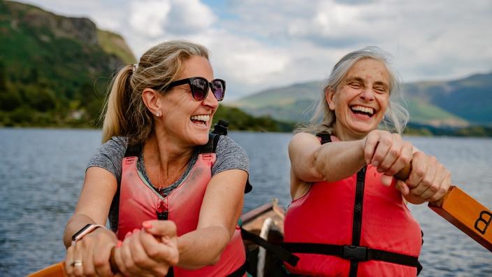 zwei gut gelaunte Frauen rudern über einen See
