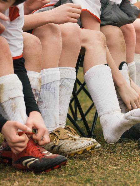 Jungen sitzen nebeneinander auf Stühlen und binden sich die Fußballschuhe zu