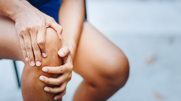 Hände, die sich ans Knie greifen