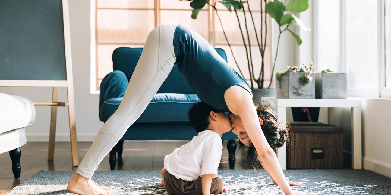 Frau absolviert die Yoga-Übung herabschauender Hund, ihr kleiner Sohn sitzt zwischen ihren Armen und Beinen