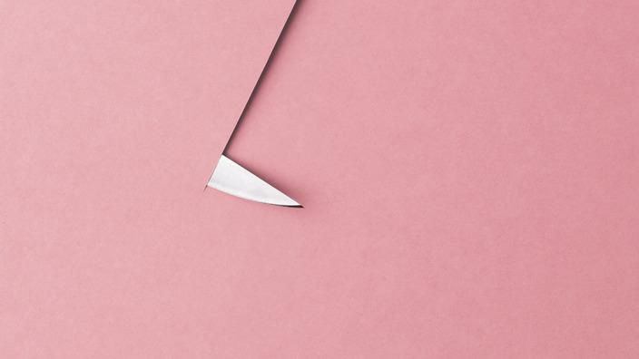 Messer durchschneidet ein rosafarbenes Blatt Papier