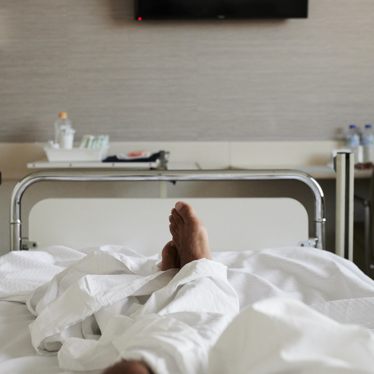 Krankenhausbett mit zwei nackten Füßen, die unter der Decke rausgucken