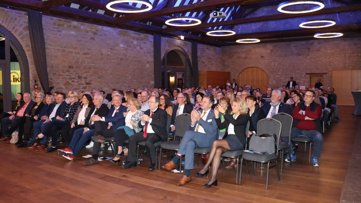 Führungskräfte und Betriebsinhaber sitzen auf Stühlen und hören sich den Vortrag an