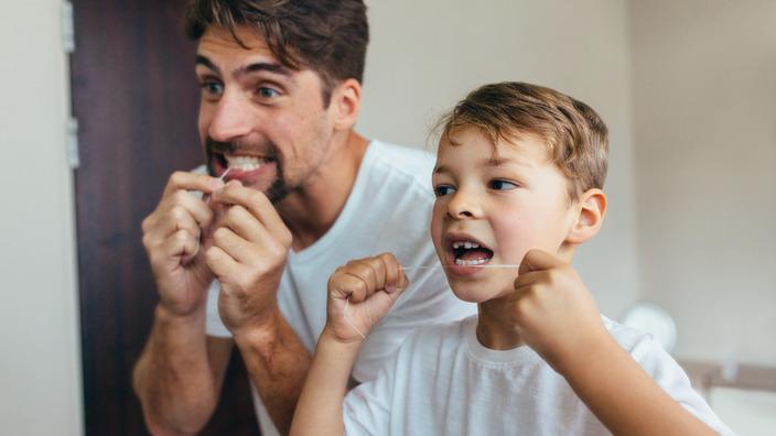 Vater und Sohn reinigen Zähne vor dem Spiegel mit Zahnseide