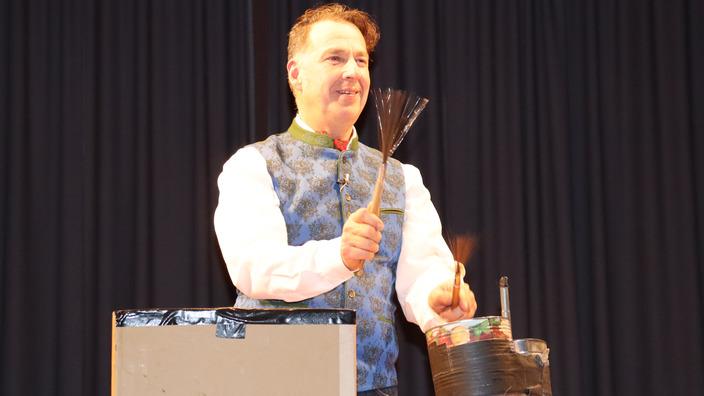 Coach Johannes Warth trommelt auf einem Pappkarton-Schlagzeug