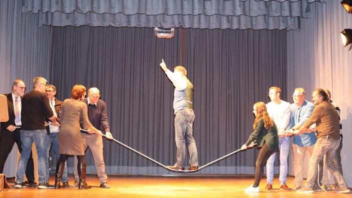 Coach Johannes Warth balanciert auf einem Seil, das von Zuschauern gespannt wird