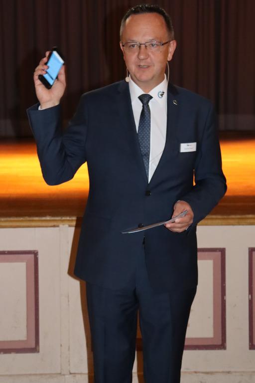 Stephan Rauch steht mit einem Smartphone in der Hand auf der Bühne
