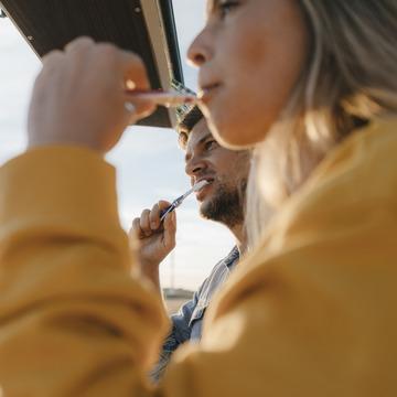 Paar steht auf einem Balkon und putzt die Zähne