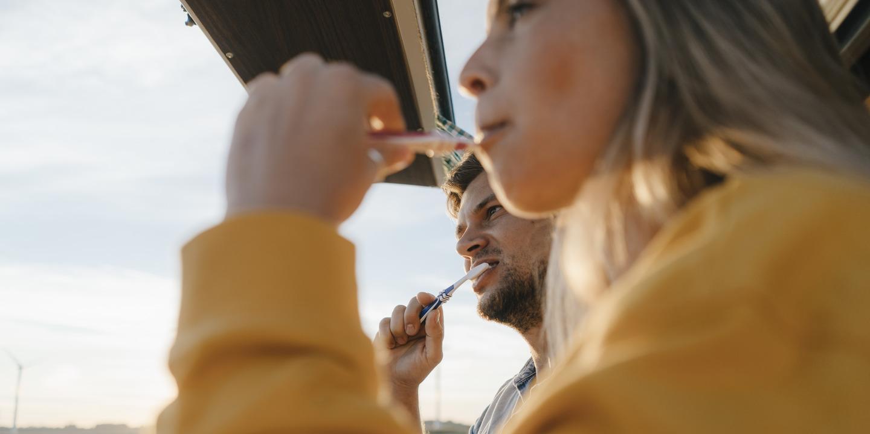 Junges Paar putzt sich die Zähne und schaut dabei aus dem Fenster