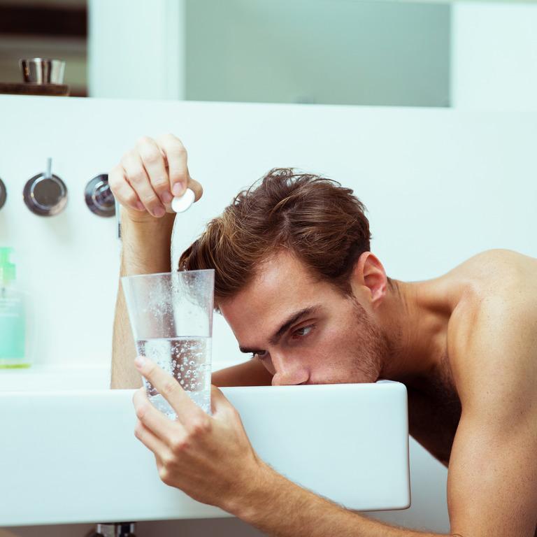 Verkaterter junger Mann liegt am Waschbecken mit einem Glas Wasser und Tablette in der Hand