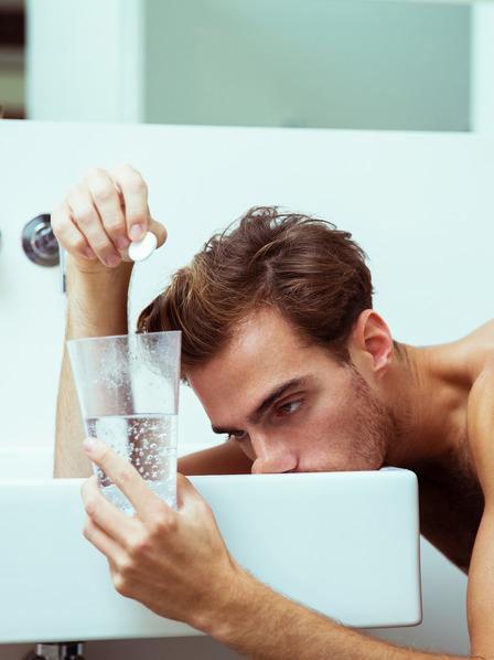 junger Mann mit einem Kater liegt mit dem Kopf auf dem Waschbecken und bereitet sich ein Glas mit Alka-Seltzer zu