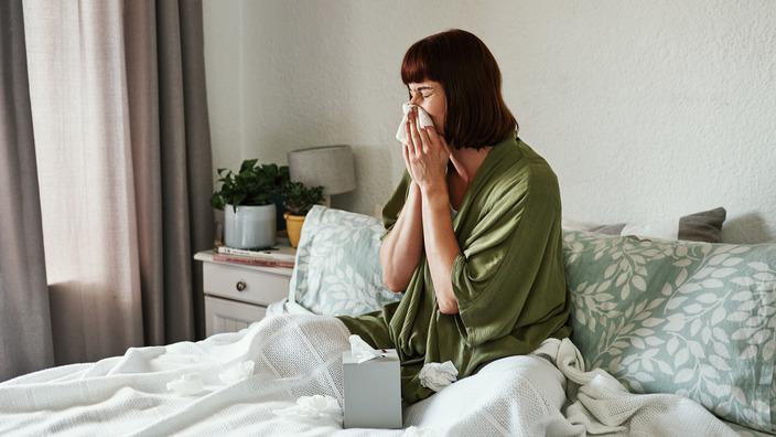 Junge Frau sitzt auf dem Bett und niest in Taschentuch