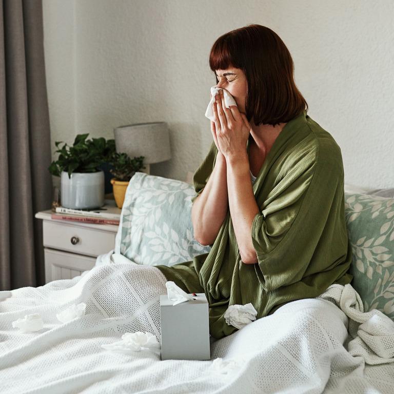 erkältete Frau sitzt im Bett und putzt ihre Nase