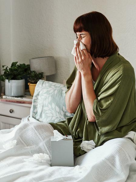 Frau sitzt auf dem Bett und niest in ein Taschentuch