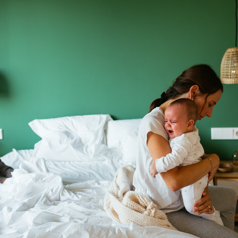 Mutter sitzt erschöpft auf dem Bett und tröstet ihr weinendes Baby, der zweijährige Bruder schaut zu