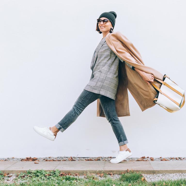 Junge Frau in Mantel, Mütze, knöchelfreien Jeans und Sneakers