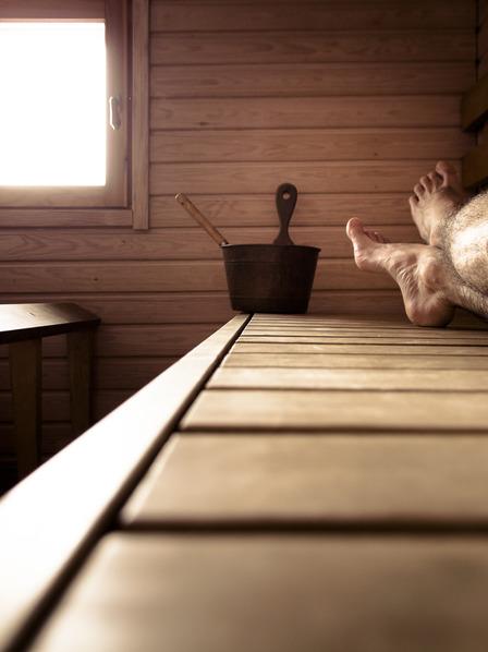 nackte Männerbeine liegen auf einer Holzliege in einer Sauna