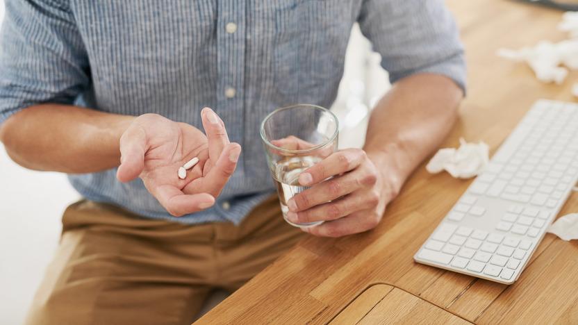 Mann sitzt am Schreibtisch und hält Tabletten und ein Glas Wasser in der Hand.