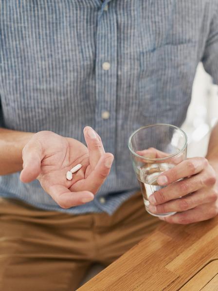 Mann sitzt an seinem Arbeitsplatz und nimmt eine Schmerztablette mit einem Glas Wasser ein