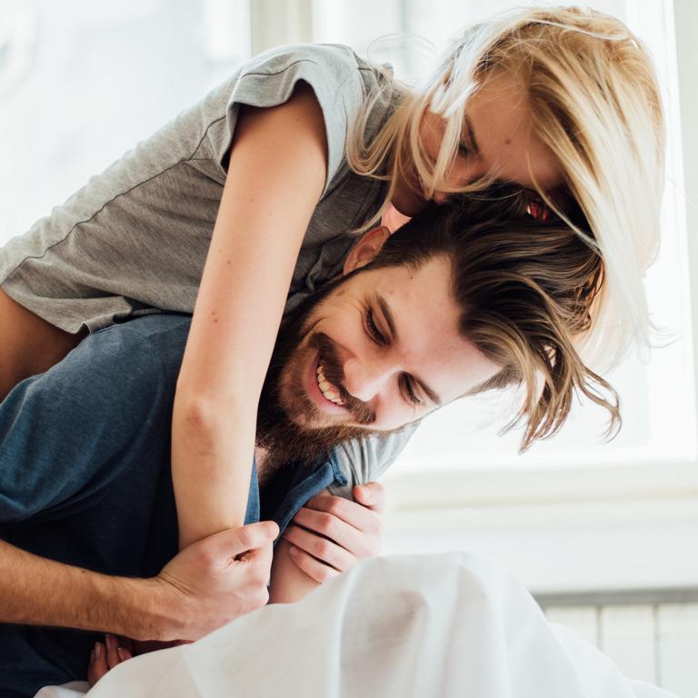 junges Paar albert auf dem Bett herum