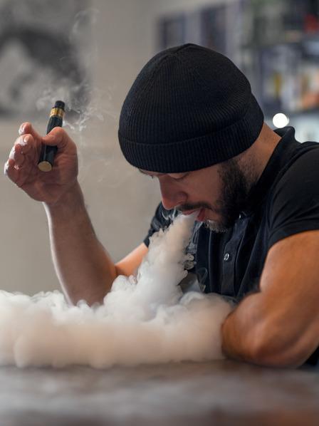 Mann bläst Dampf aus seiner E-Zigarette