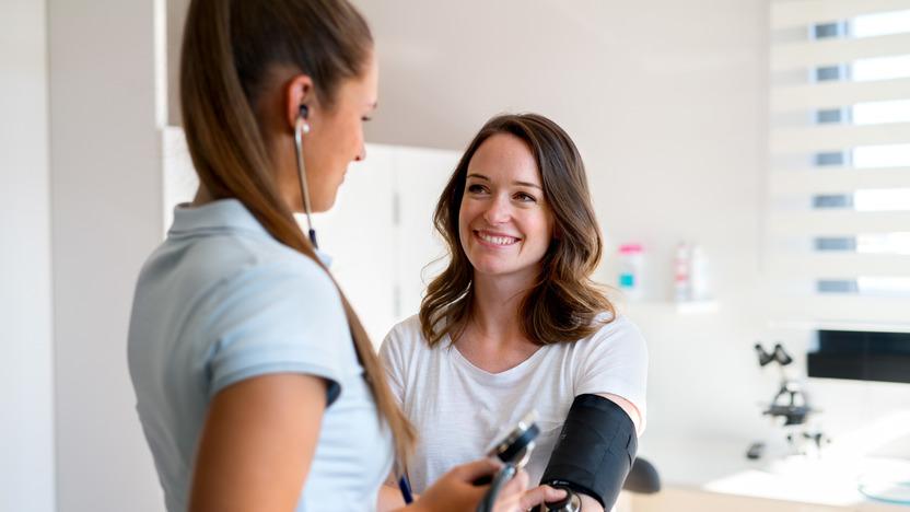 Frau lässt bei einem Gesundheits-Check-up von Ärztin den Blutdruck messen.