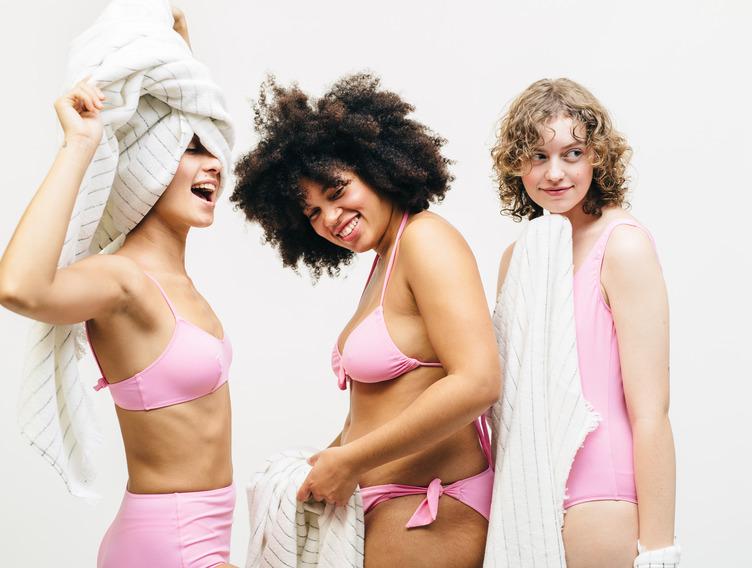 Drei Frauen in pinker Badekleidung und mit Handtüchern.
