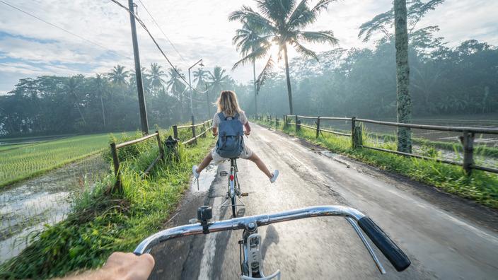 zwei junge Urlauber fahren mit dem Rad zwischen Reisfeldern auf einer kleinen vietnamesischen Landstraße