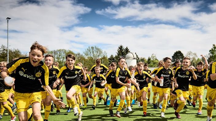 Junge Fußballer im BVB-Outfit laufen über den Rasen