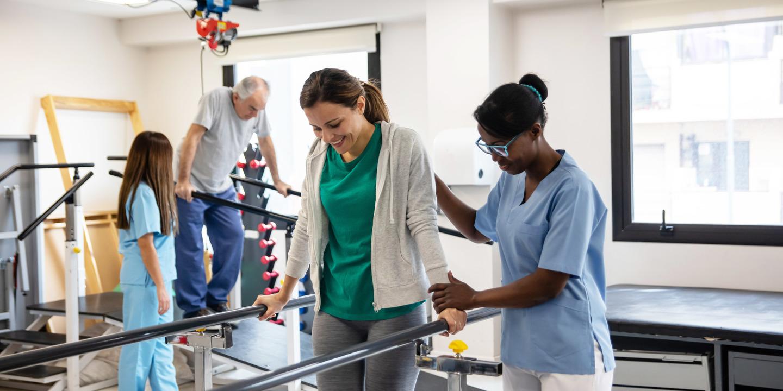 Reha-Patienten lernt mit einer Physiotherapeutin wieder zu laufen
