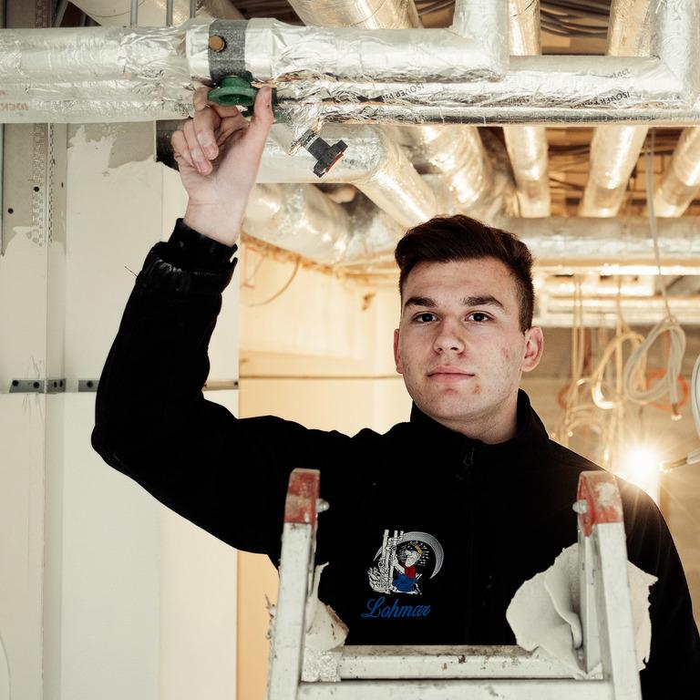 Junger Mann in Arbeitskleidung steht auf einer Leiter und prüft Rohre an der Decke