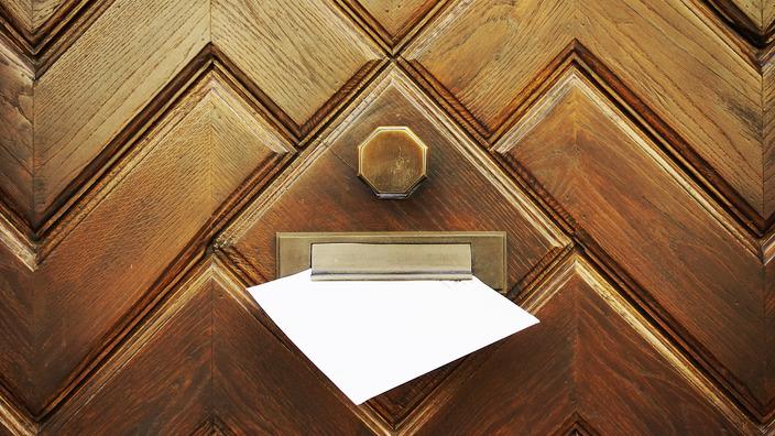Briefumschlag hängt im Briefschlitz einer Haustür