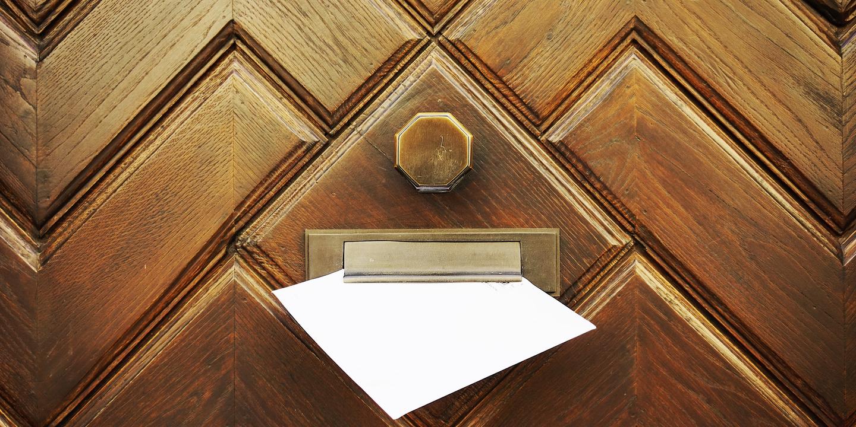 Briefumschlag mit Mitgliedsbescheinigung steckt im Briefschlitz einer Haustüre