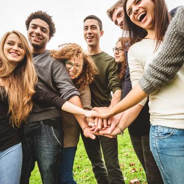 Gruppe von Freunden steht im Halbkreis und streckt einen Arm aus, um die Hände übereinander zu legen