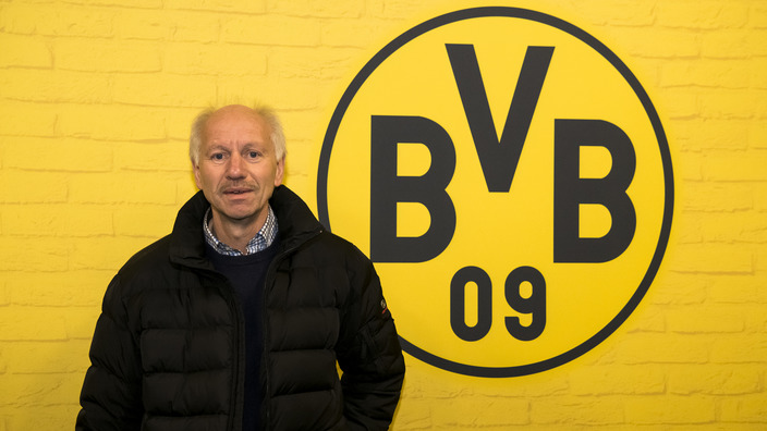 Wolfgang Spenner steht vor einer gelben Wand mit BVB-Logo