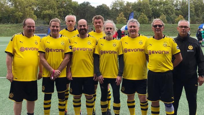Gruppenbild älterer Herren im BVB-Trikot