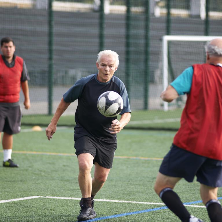 Ältere Männer beim Fußballspielen auf dem Fußballplatz