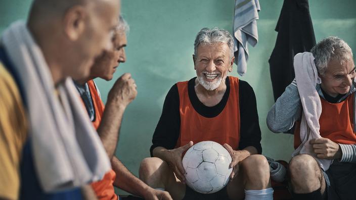 Ältere Männer sitzen lachend in Umkleidekabine, ein Mann hält einen Fußball in den Händen